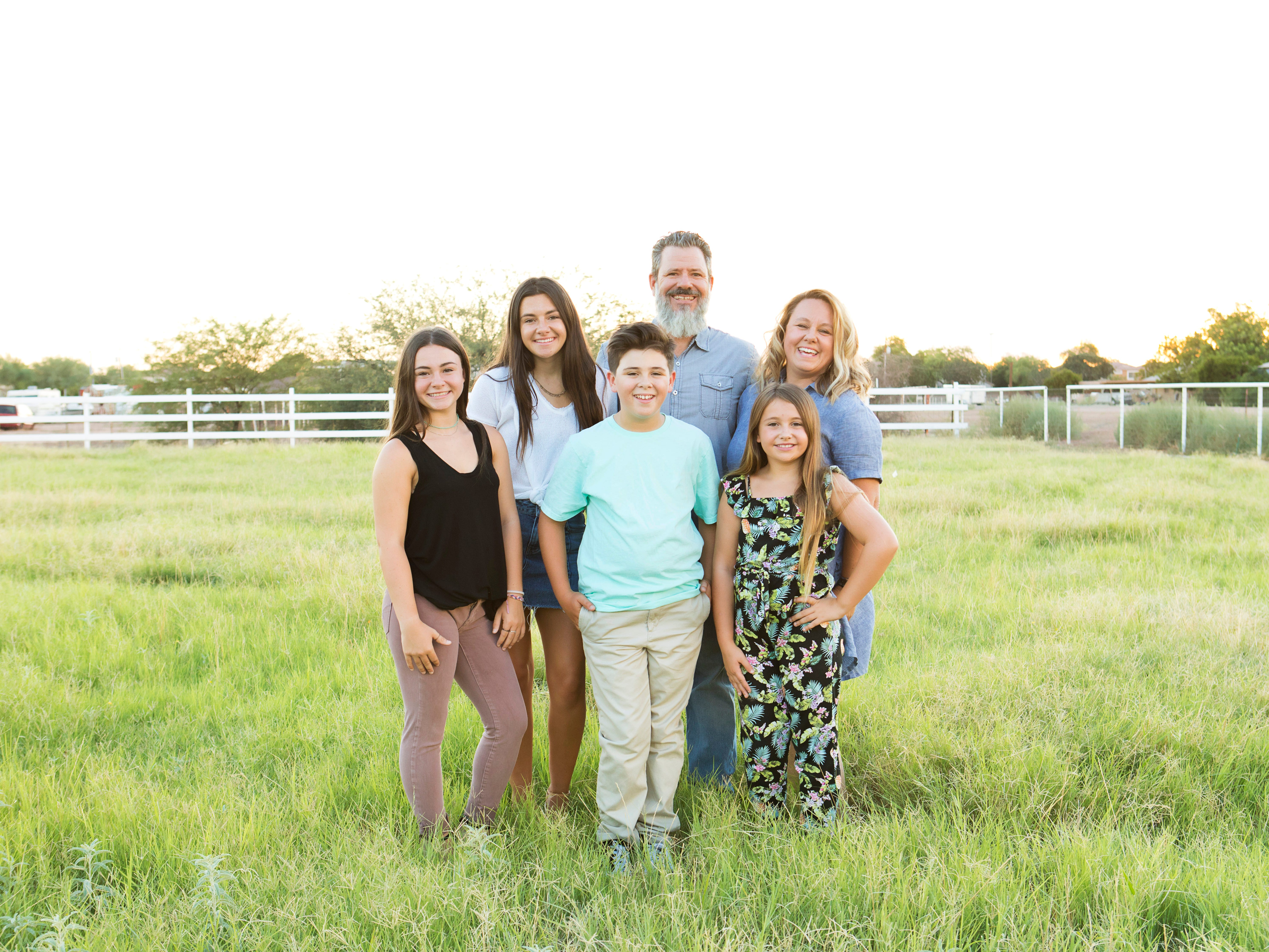 Ryan and Jenn Sutton with their four kids posing on their meadow. Jenn, a photographer, was inspired by the home's potential for photo opportunities. Ryan runs a mortgage bank in Scottsdale with his father.