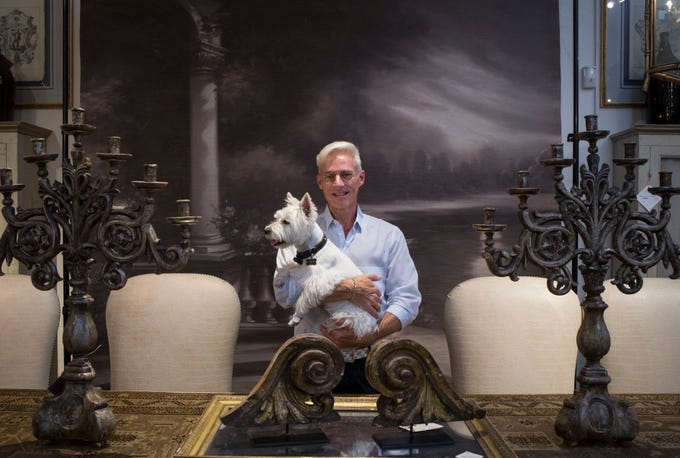 Timothy Harris holds his dog, Tasha, July 26, 2018, at Relics Architectural Home & Garden in Phoenix.