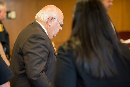 Graham Rummel is lead to the podium for a probable cause hearing Tuesday, Aug. 7, 2018, in Judge Monaghan's courtroom in Port Huron. Rummel, a retired Clay Township police officer, is facing five criminal charges associated with an April 11 incident in St. Clair.
