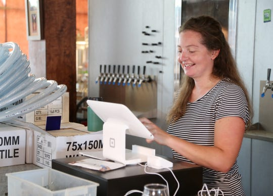 Caroline Bergelin sets up the Square cash register at Kings Court Brewing in the City of Poughkeepsie on August 7, 2018.