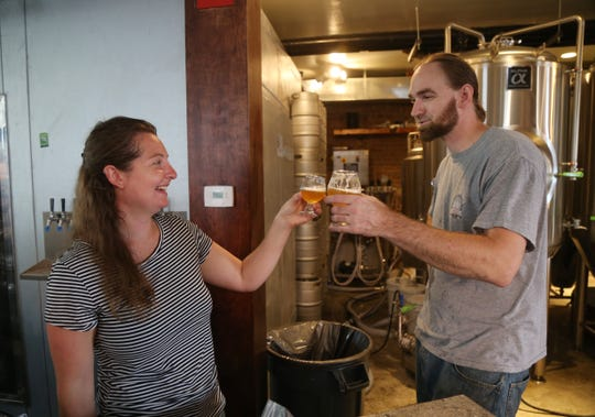 Caroline Bergelin and Cortlandt Toczylowski toast to another day of making beer at Kings Court Brewing in the City of Poughkeepsie on August 7, 2018.