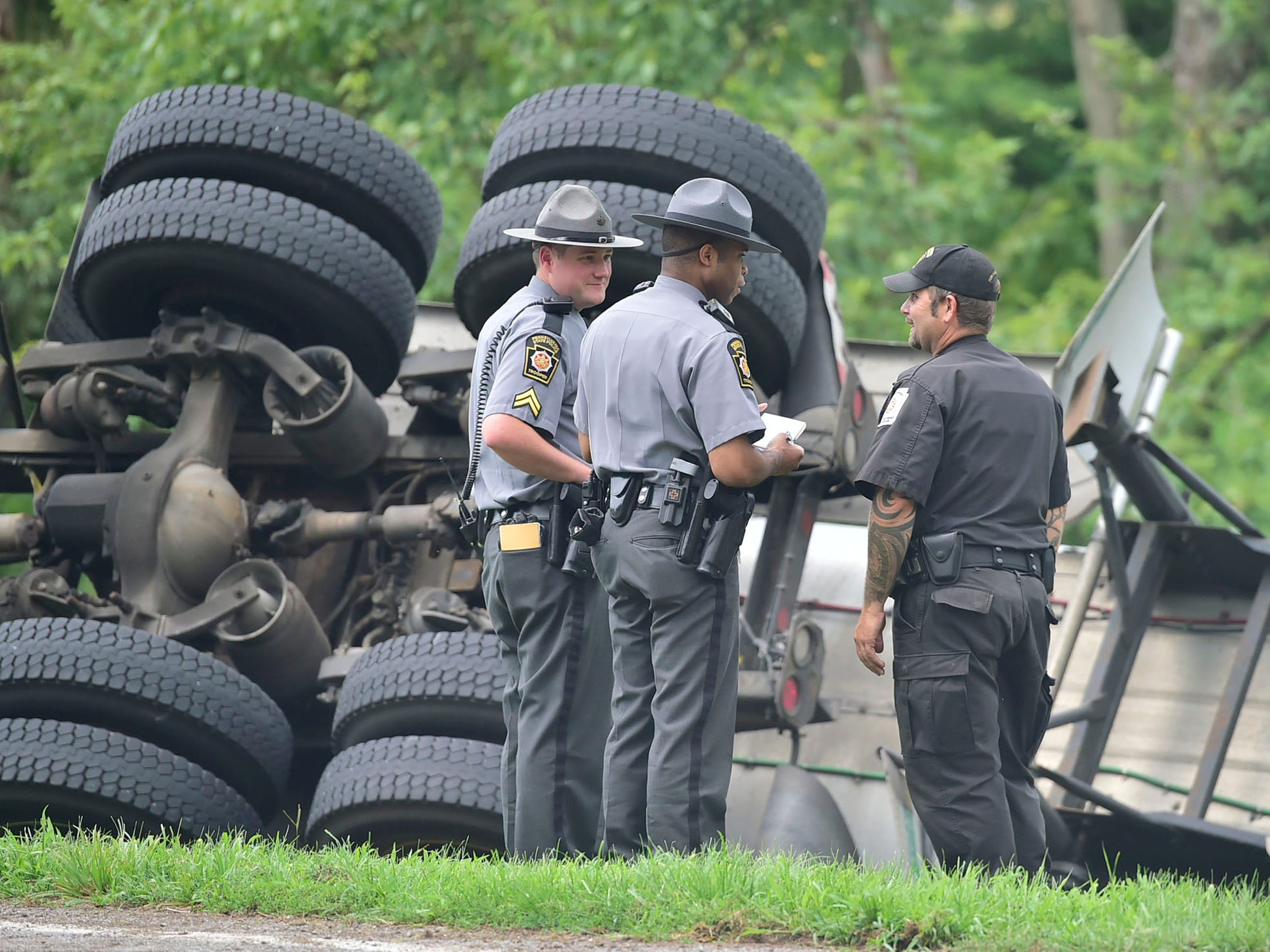 A tractor-trailer, hauling liquid tar, overturned across from 456 Siloam Road, Greene Township, just before 12:30pm, Tuesday, August 7, 2018. The driver was not injured in the crash. The street is closed at Airport Road as state police investigate. Firefighters are trying to contain the flow of oil and keep it out of the nearby creek.