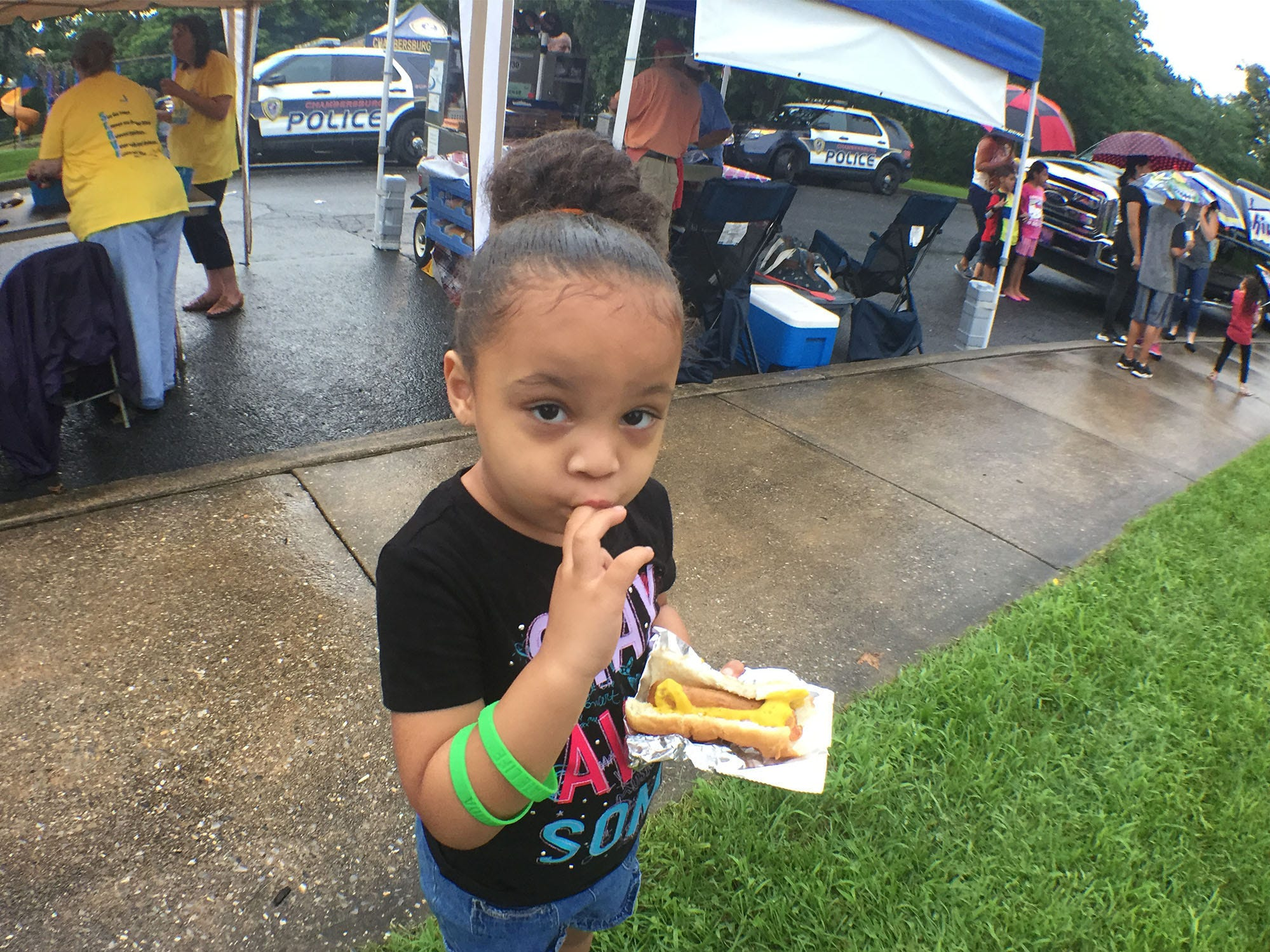 Jalaina Acosta, 3, licks mustard off her Pap's Dog Stop hot dog. Chambersburg Police Department National Night Out was held Tuesday, August 7, 2018 at the Franklin County Housing Authority complex. The annual event is designed to have community members get a chance to meet first responders.
