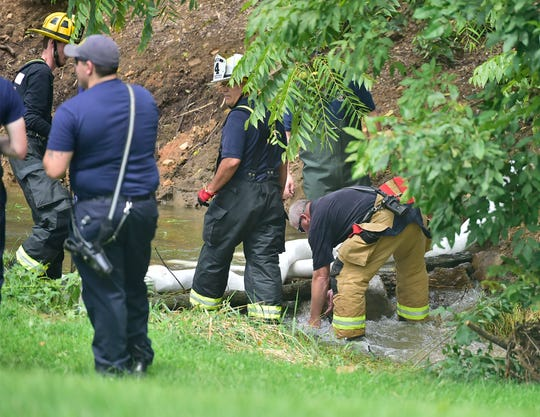 Firefighters contain liquid in a creek. A tractor-trailer, hauling liquid tar, overturned across from 456 Siloam Road, Greene Township, just before 12:30pm, Tuesday, August 7, 2018. The driver was not injured in the crash. The street is closed at Airport Road as state police investigate. Firefighters are trying to contain the flow of oil and keep it out of the nearby creek.
