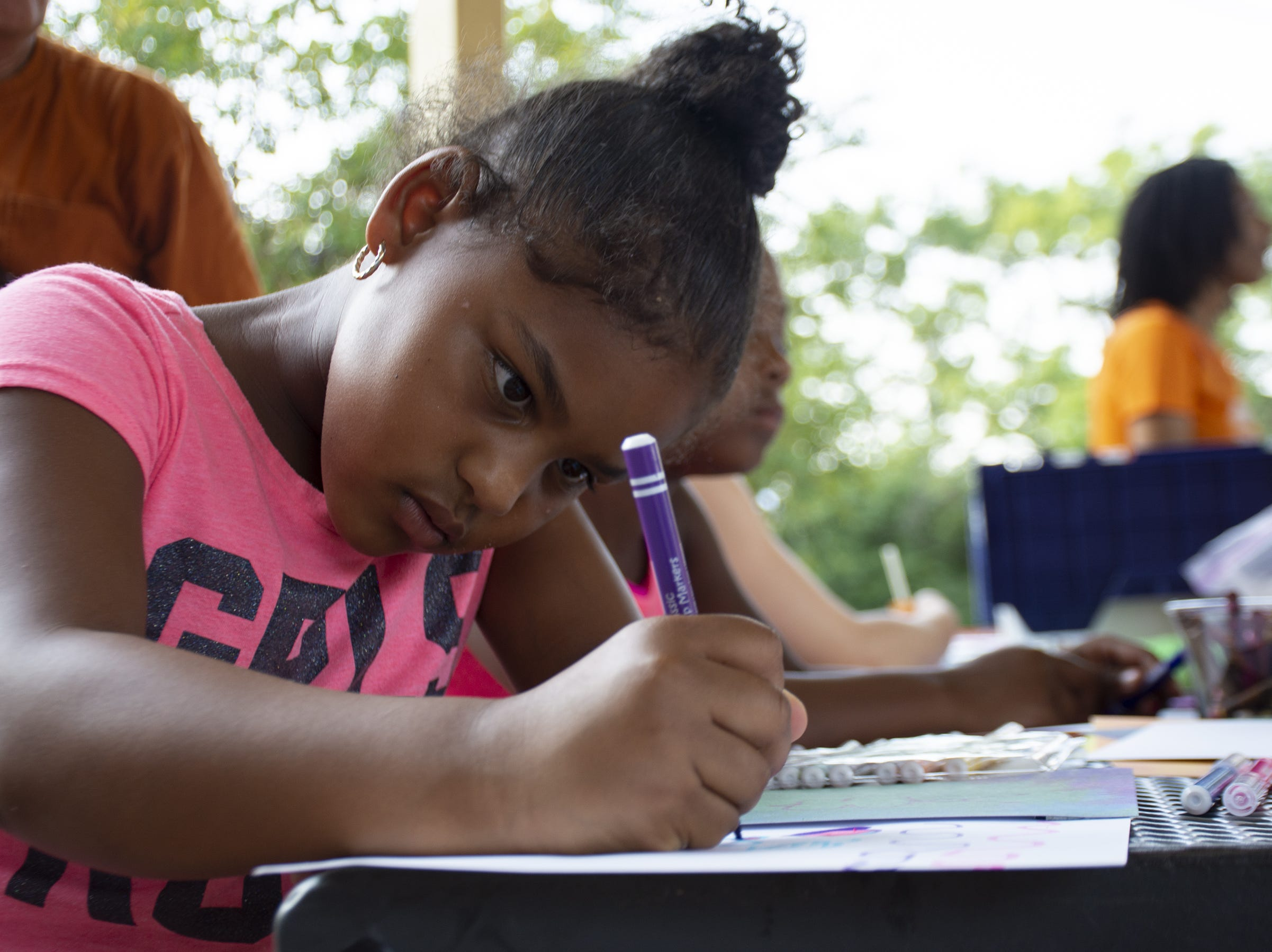 Za'niyah Smallwood, 7, colors her drawing at the Art in The Parks event at Renaissance Park in York on Monday night.