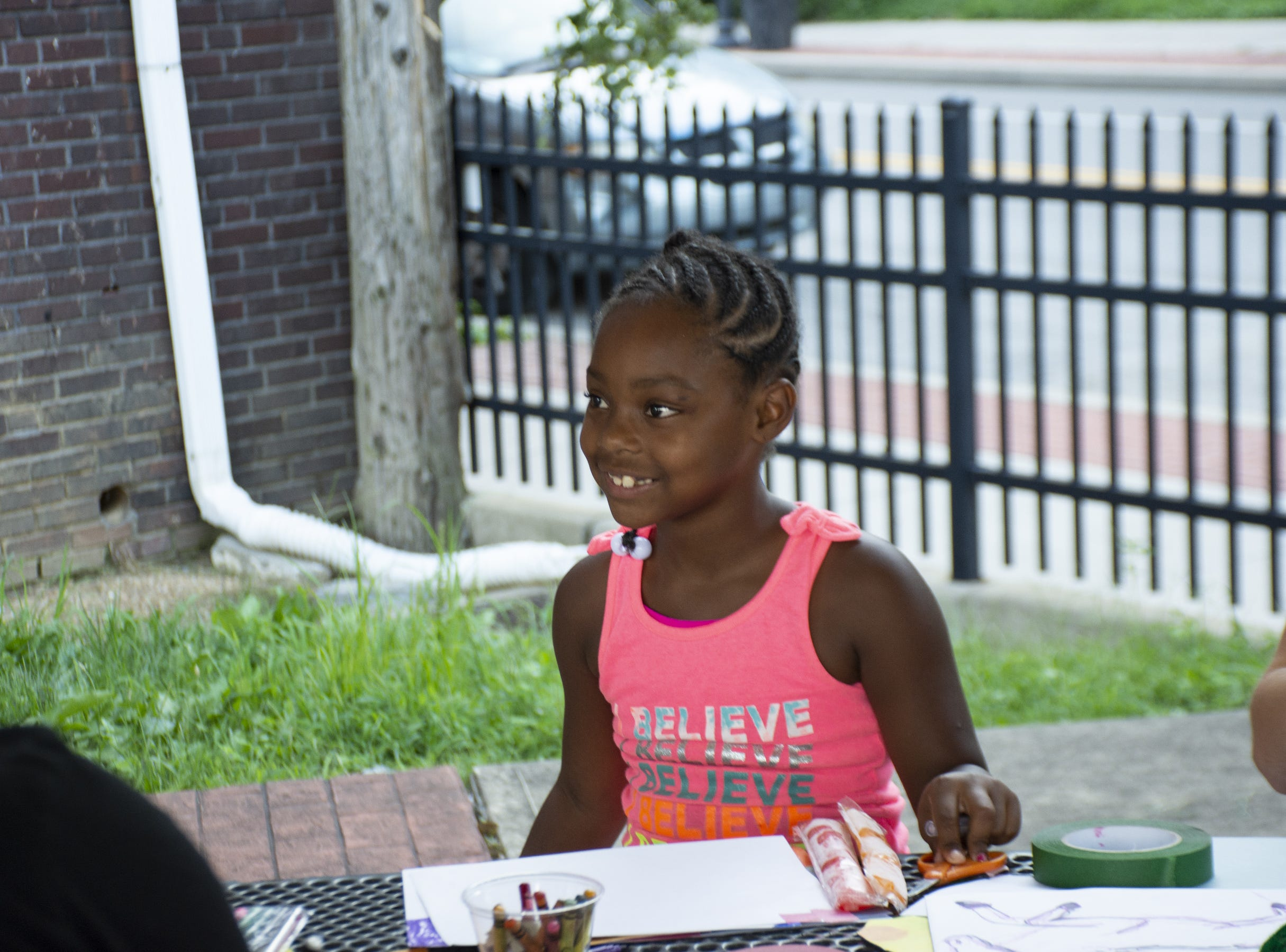 Kee'maiyan Cross, 7, pays attention to a story that one of the coordinators is telling to her at the Art in the Parks event in Renaissance Park in York on Monday.