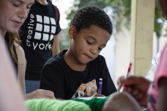 Jahlil Brown, 5, colors one of his drawings at Art in the Parks on Monday.