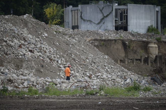 A worker from Renascent is dwarfed by a pile of rubble at the site of the former Reid Hospital campus on Tuesday, Aug. 7, 2018.