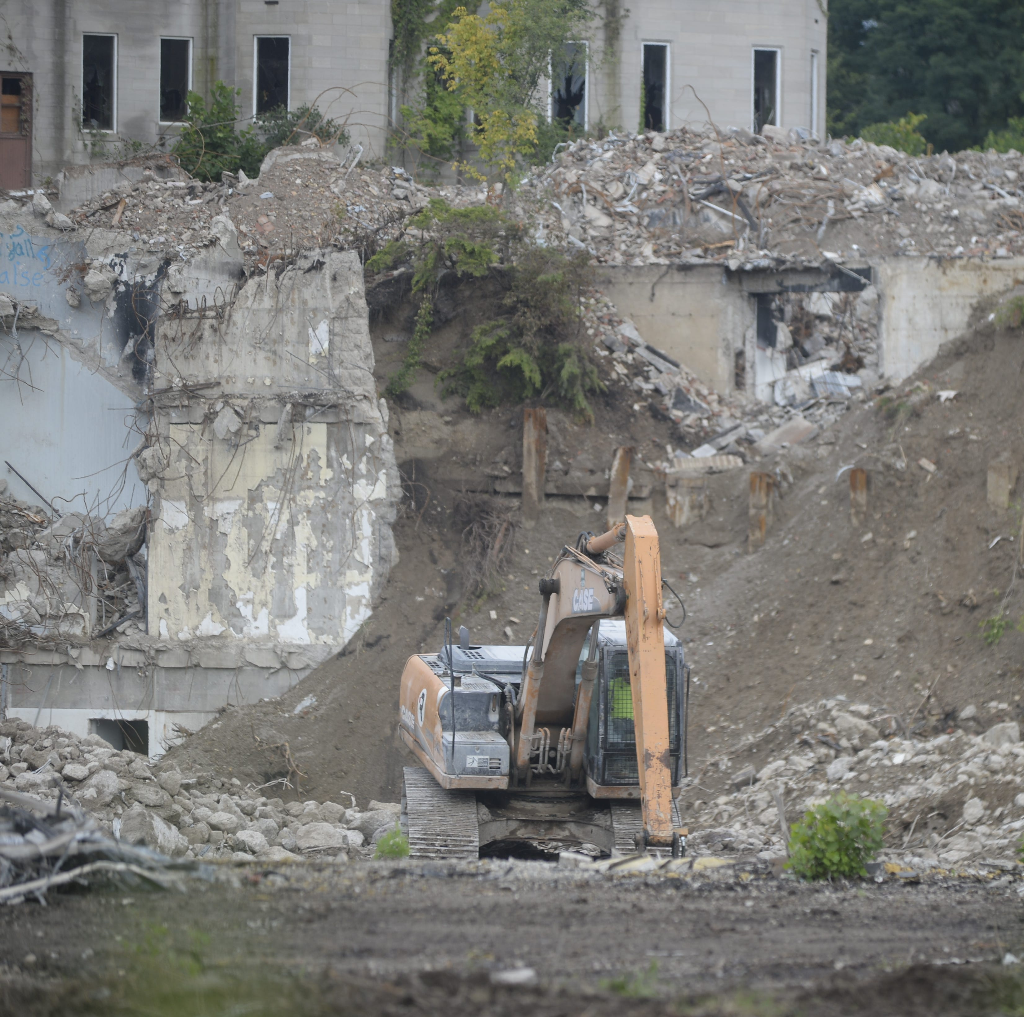 Workers from Renascent on Tuesday morning sort through debris in the hole created by the demolition of Leeds Tower and the service wings of the former Reid Hospital campus.