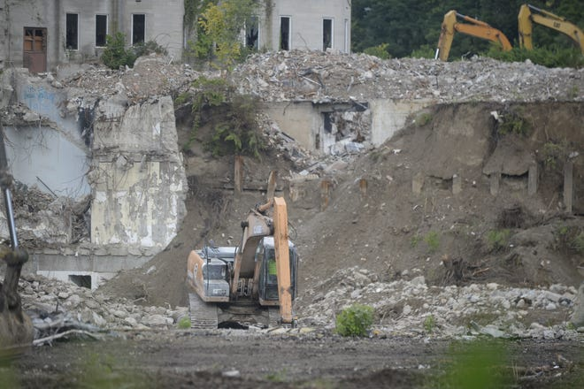 Workers from Renascent on Tuesday, Aug. 7 sort through debris in the hole created by the demolition of Leeds Tower and the service wings of the former Reid Hospital campus.