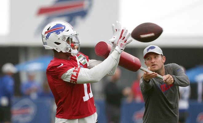Receiver Zay Jones works with offensive assistant Shea Tierney during passing drills at Bills training camp.