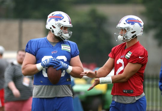 Center Russell Bodine (66) and quarterback Nathan Peterman work on some details during training camp.