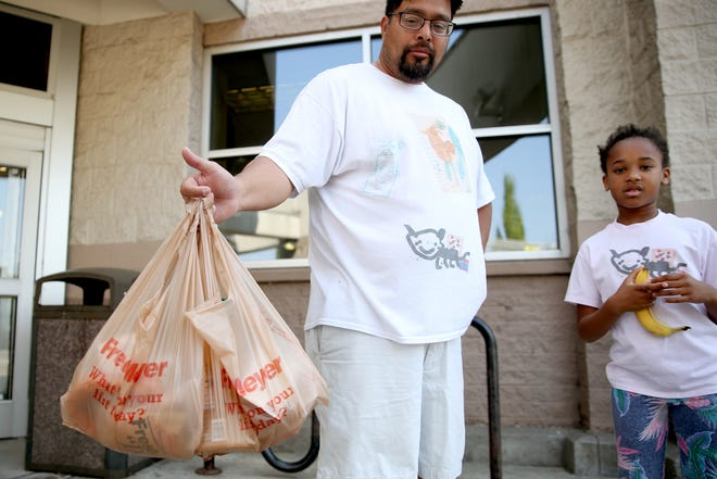 """Armando Martinez, 45, and his daughter Zoë Martinez, 8, of Salem, use plastic bags at the Fred Meyer on Commercial St. SE in Salem on Tuesday, Aug. 7, 2018. A proposed ban on single-use plastic bags will come before the Salem City Council on Aug. 27. """"[A plastic bag ban] wouldn't really bother me at all,"""" Armando Martinez said. """"We pay a tax already on plastic bottles, so it wouldn't really be different."""""""