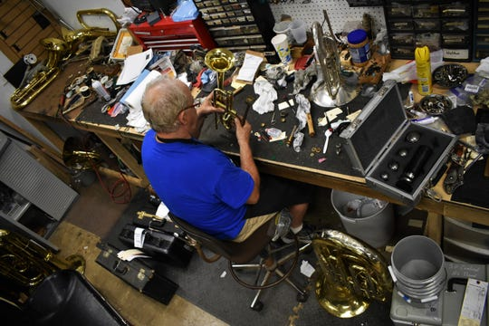 Ronnie Atwood, the brass repair technician at Tarpley Music, fixes a trumpet at his workbench on July 30, 2018.