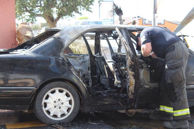 Officials investigate interior of the vehicle that caught on fire Aug. 7, 2018 at Sunset Mall.