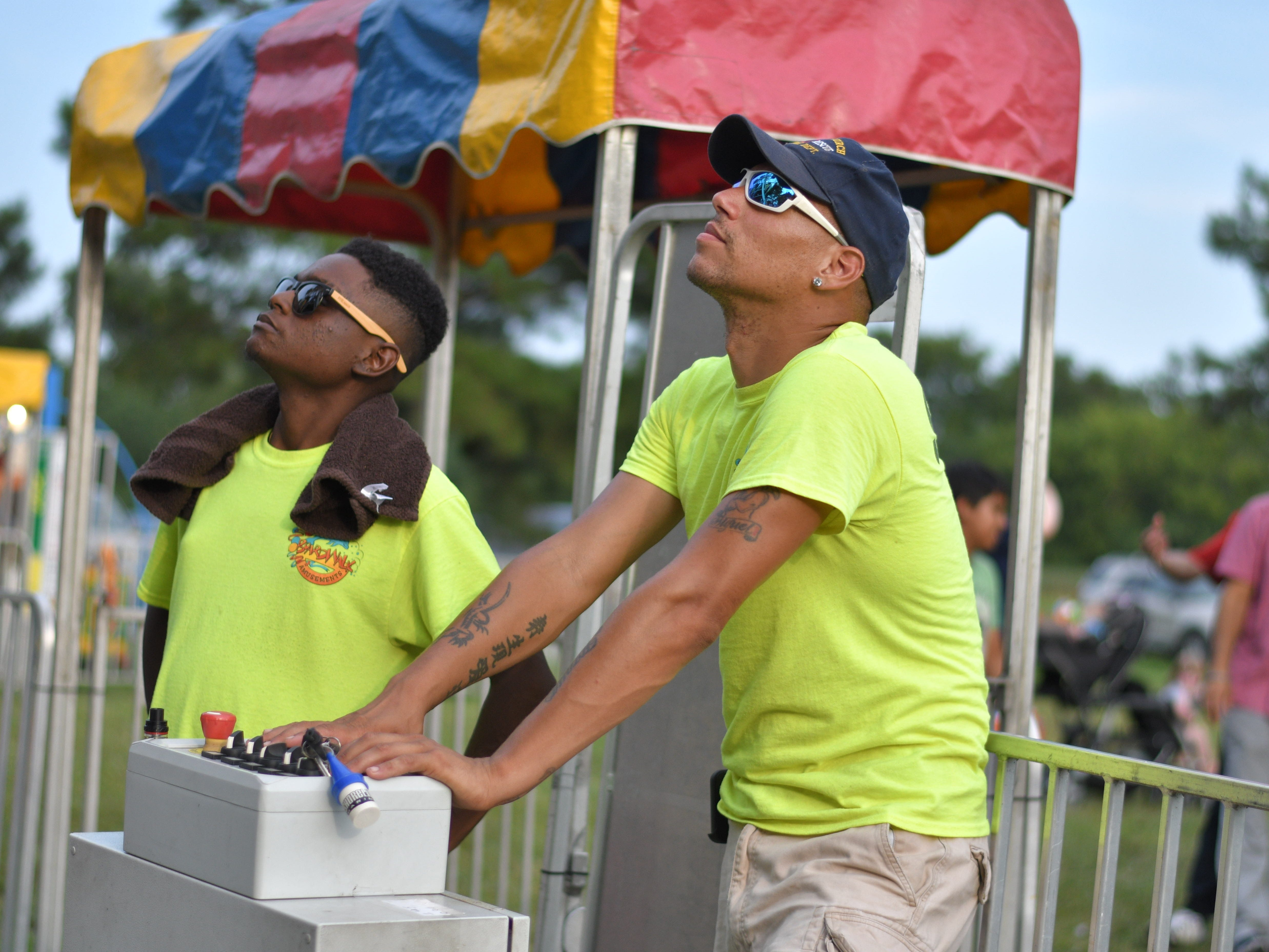Volunteers Adam Fisher, left, and Jose Guilarte run the ferris wheel during the Cape Charles Volunteer Fire Company Carnival.
