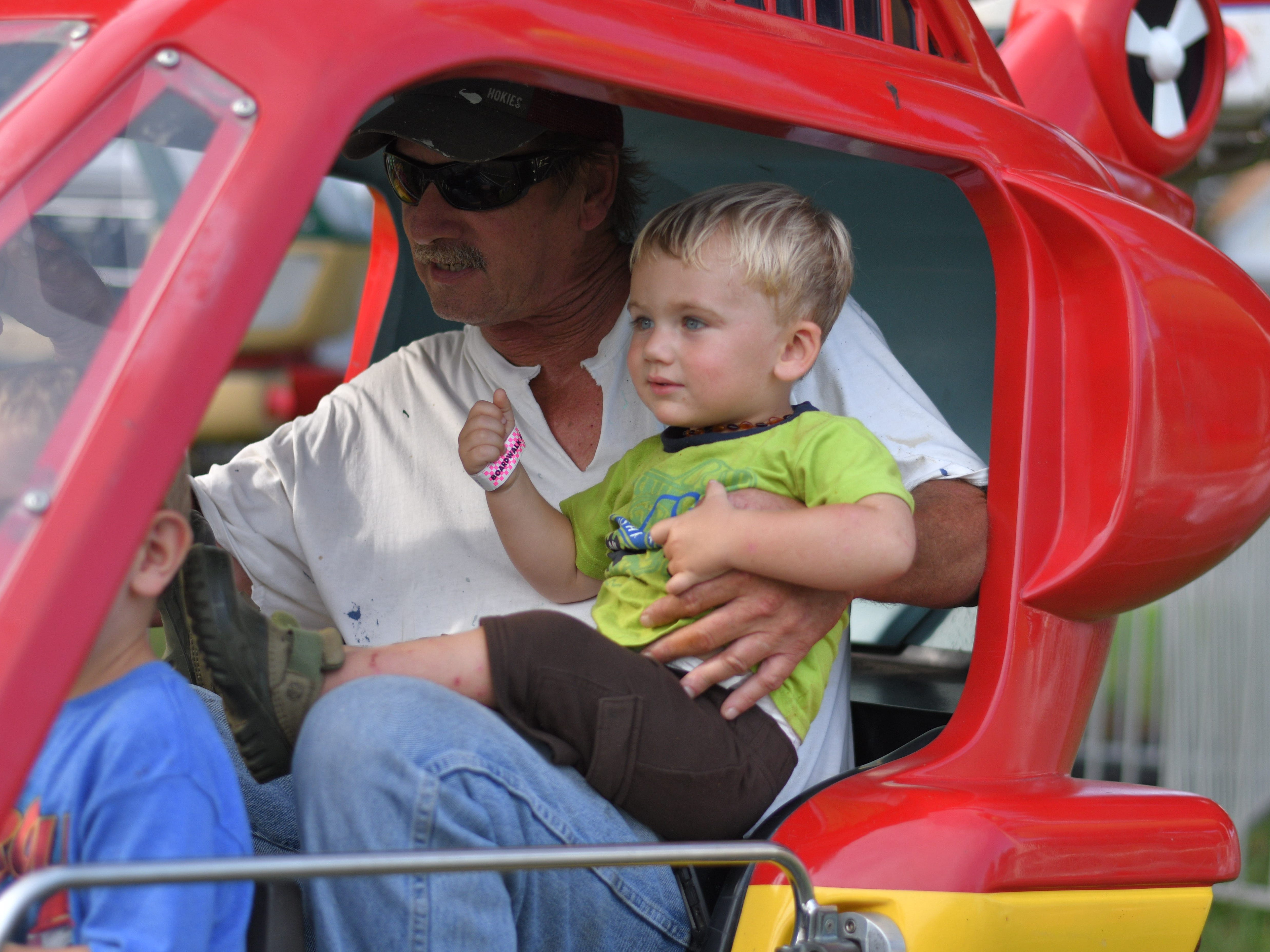 Bill Widgeon rides with his grandson, Colt Champion, at the Cape Charles carnival.