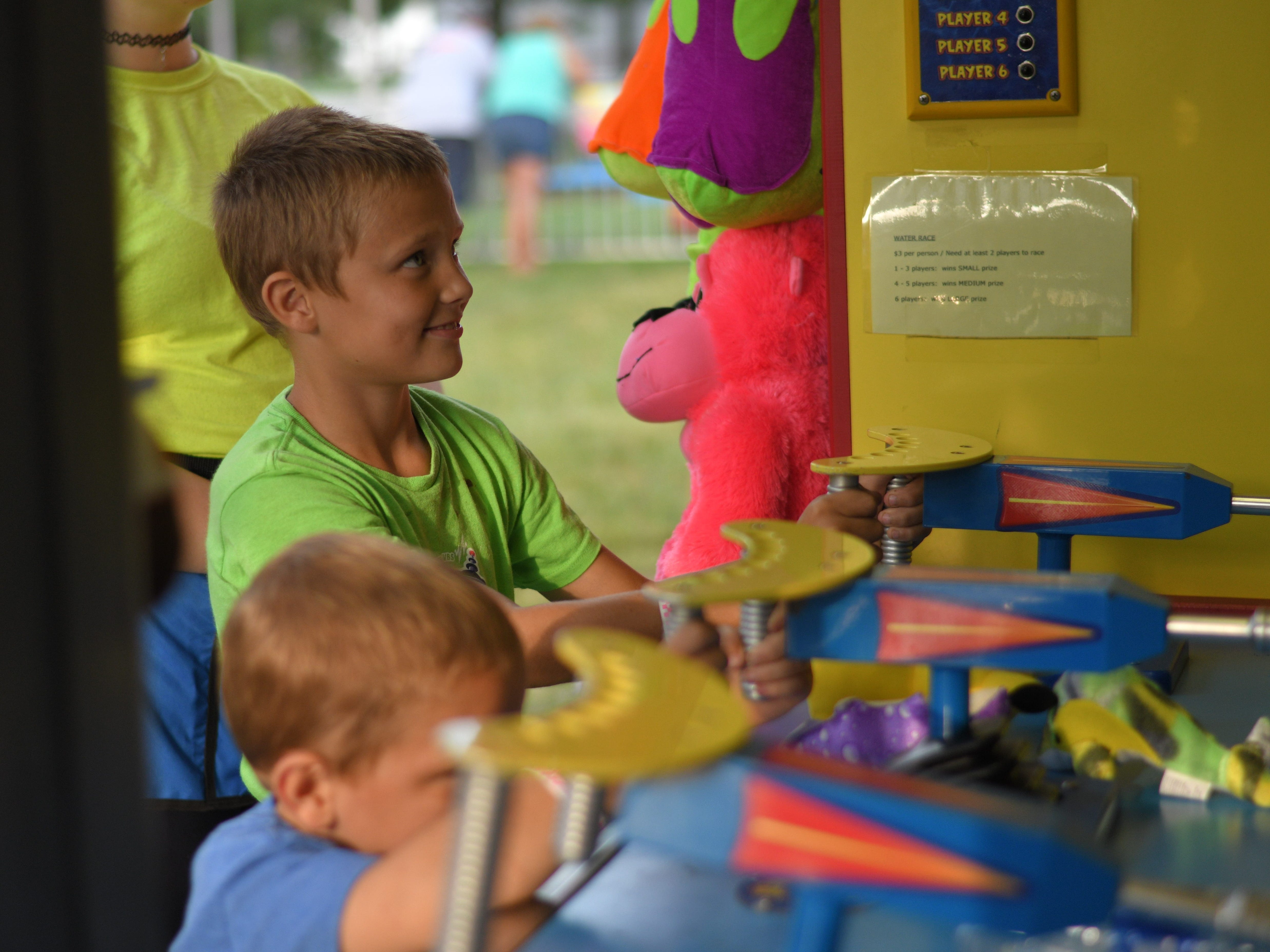 Caleb Champion concentrates on a carnival game at the Cape Charles Volunteer Fire Company Carnival.
