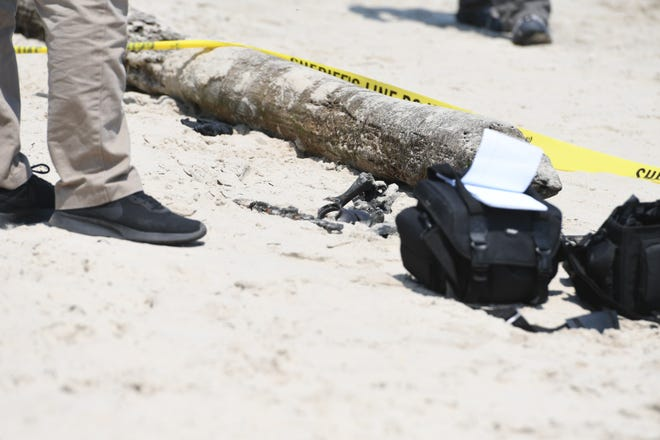 Items recovered from the suitcase are shown on the beach.
