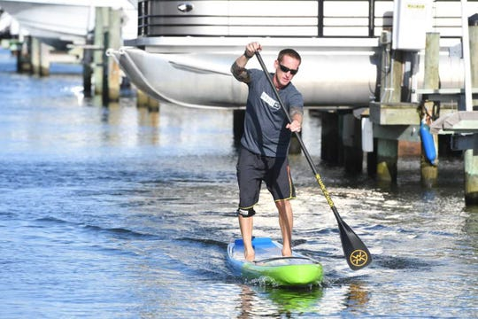 Wayne Best paddles down the canal in front of his house in Ocean City.
