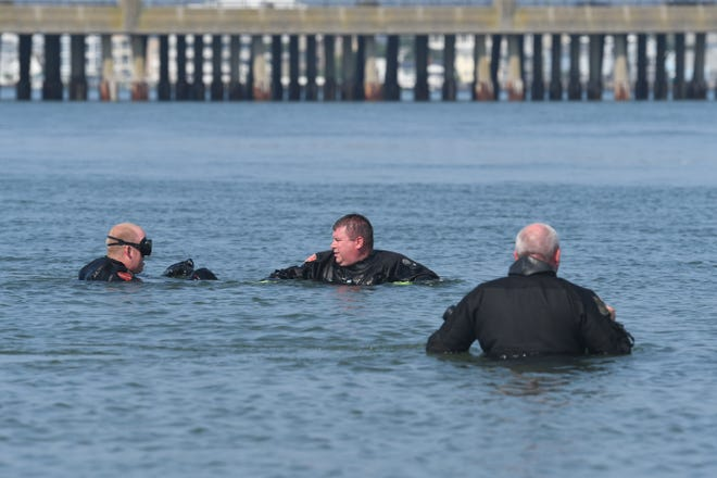Investigators search the water after a suitcase of bones was found on a west Ocean City beach.