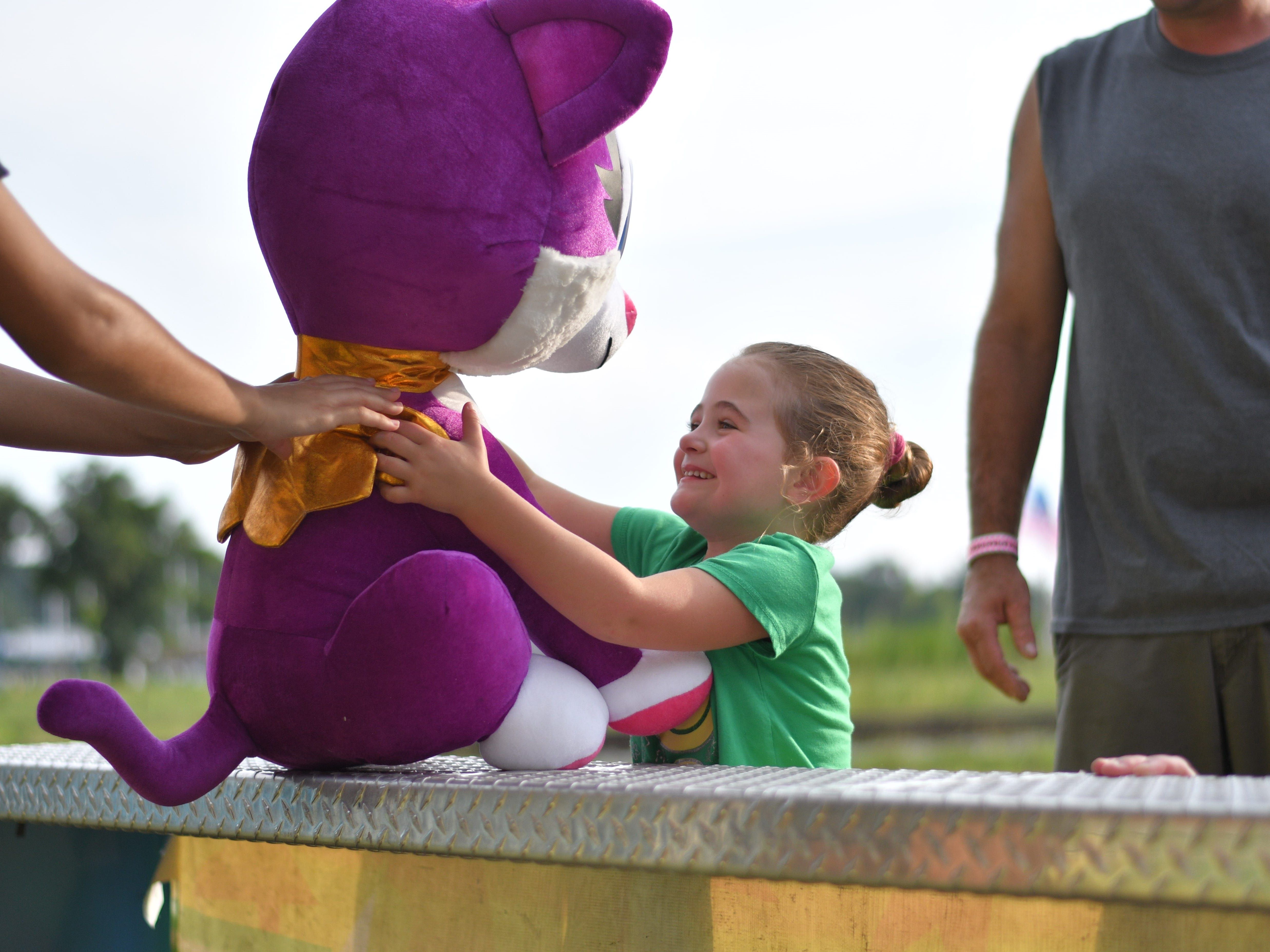 Mia Evans is handed her stuffed prize during the Cape Charles Volunteer Fireman's Carnival.