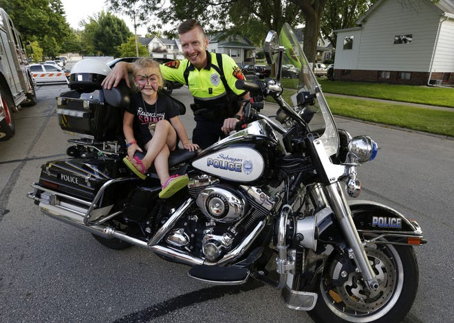 Jillian Lamb, 3, of Sheboygan, sits upon a police motorcycle by Sheboygan Police Officer Dustin Pickett during National Night Out, Aug. 1, 2017, in Sheboygan.