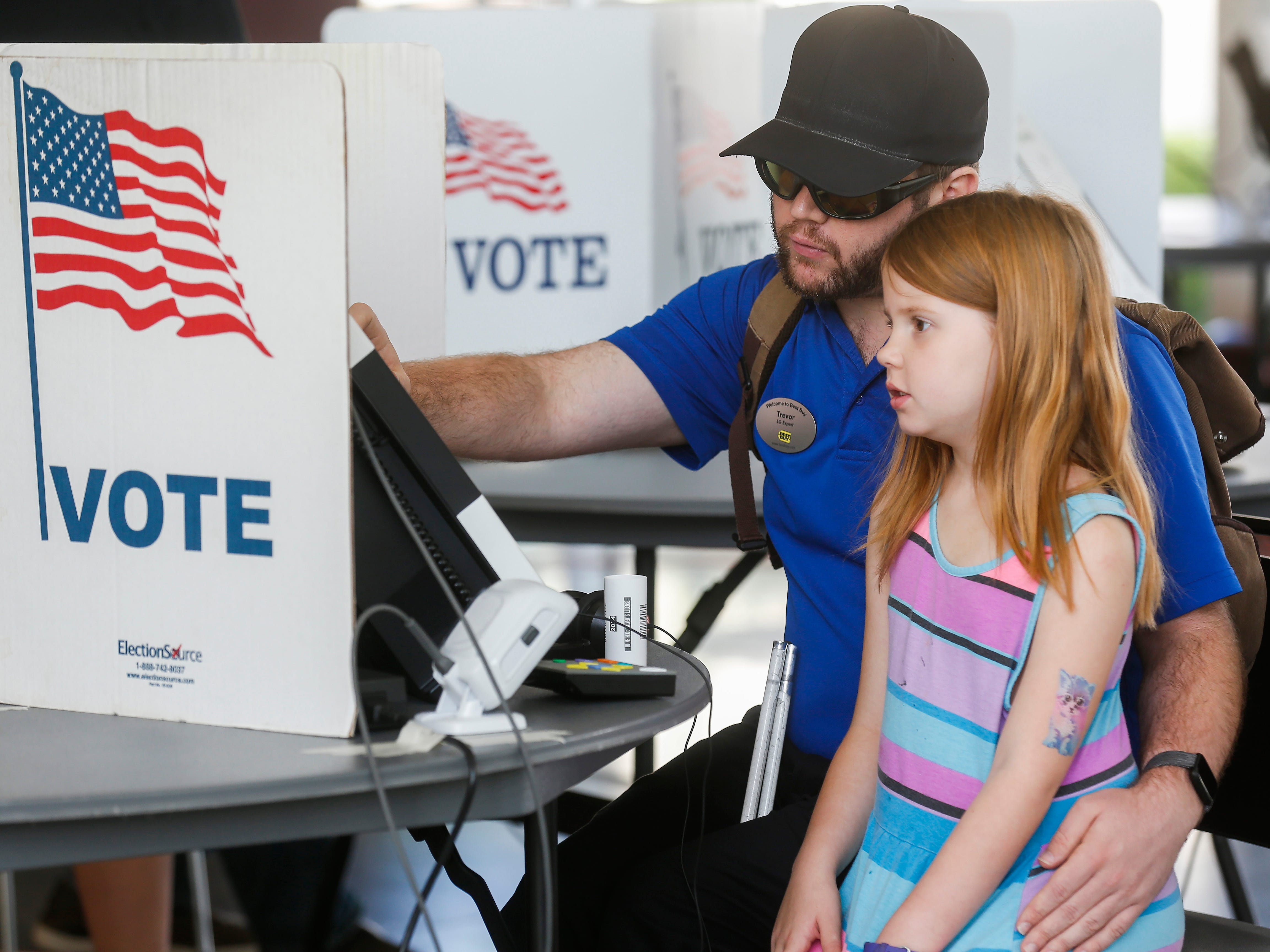 Trevor Knoblauch votes with his daughter Aiowin Knoblauch, 7, at the Davis-Harrington Welcome Center at Missouri State University on Tuesday, Aug. 7, 2018.