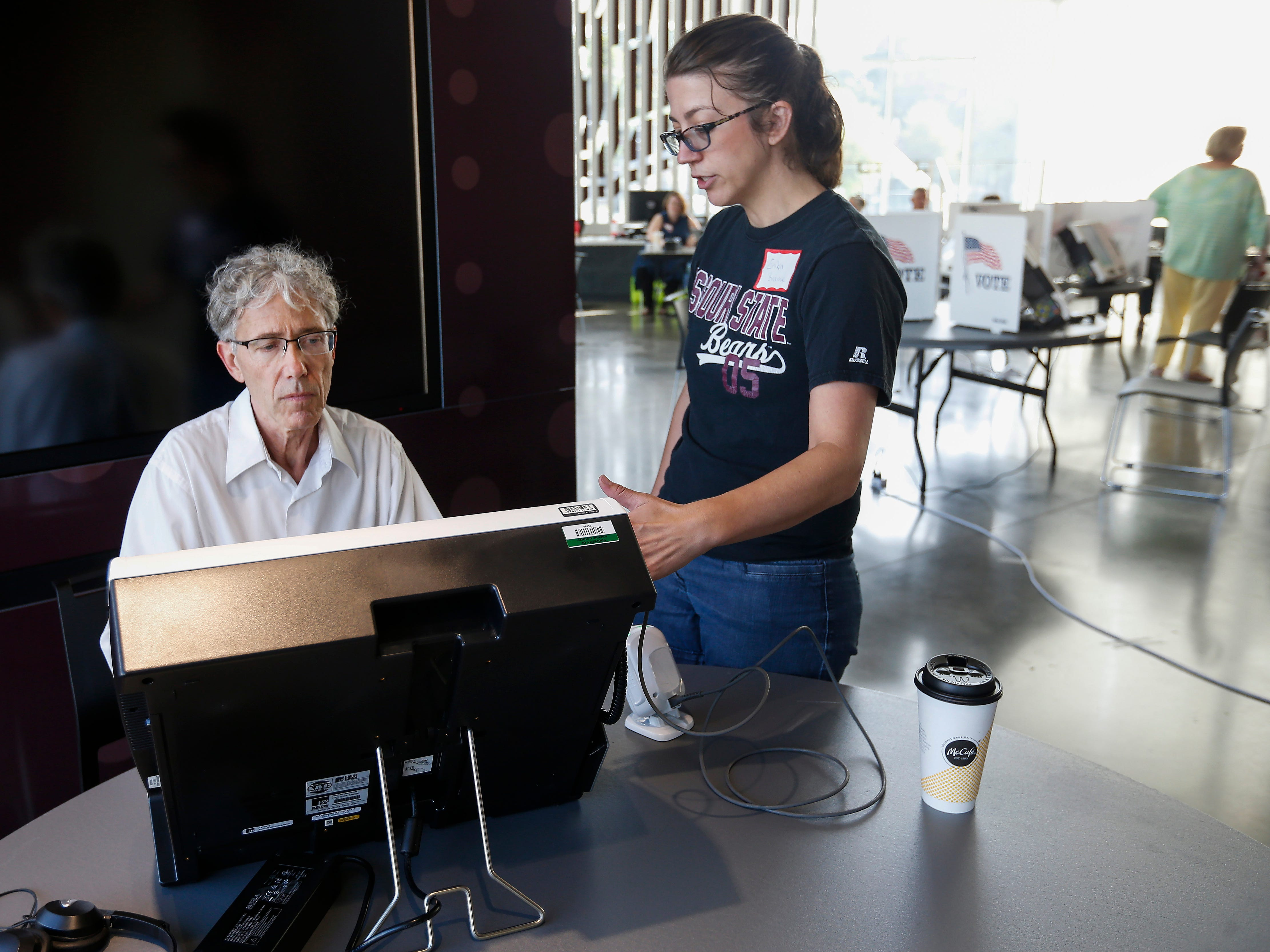 Election judge Erika Brame shows Mike Wills how to use the Express Vote machine at the Davis-Harrington Welcome Center at Missouri State University on Tuesday, Aug. 7, 2018.