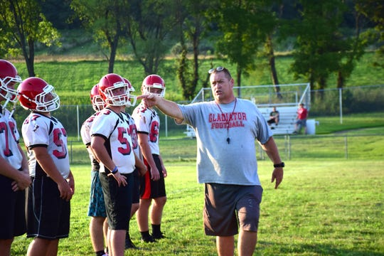 Robert Casto, Riverheads' head football coach, explains an offensive formation to his players during their first practice of the season on Monday, Aug. 6, 2018, at Riverheads High School in Greenville, Va.
