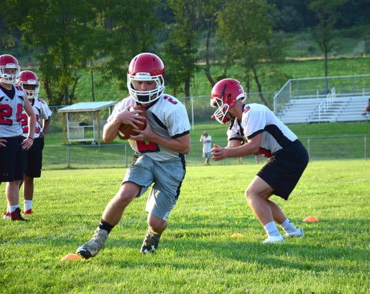 A Riverheads running back takes a handoff during the Gladiators' first football practice of the season on Monday, Aug. 6, 2018, at Riverheads High School in Greenville, Va.