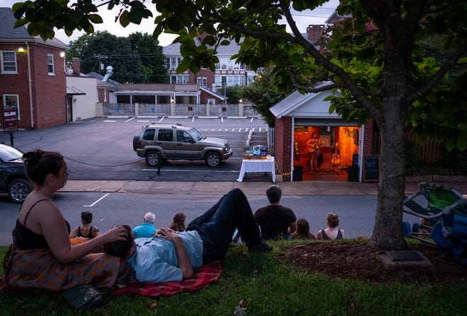People gather near the Garage, a small music venue in Charlottesville, Va. Residents say that since last year's violence, they have learned lessons and opened their eyes to truths they previously weren't forced to face.