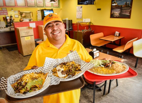 Giliberto's Mexican Taco Shop owner Aldo Coconi holds some of the customers favorites Monday, Aug. 6, in St. Cloud.