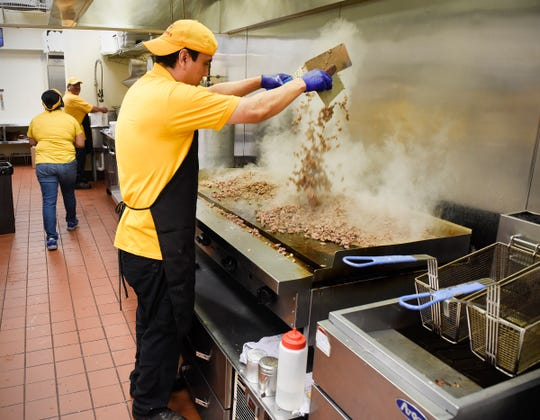 Gabriel Salas browns meat on the grill at Giliberto's Mexican Taco Shop Monday, Aug. 6, in St. Cloud.