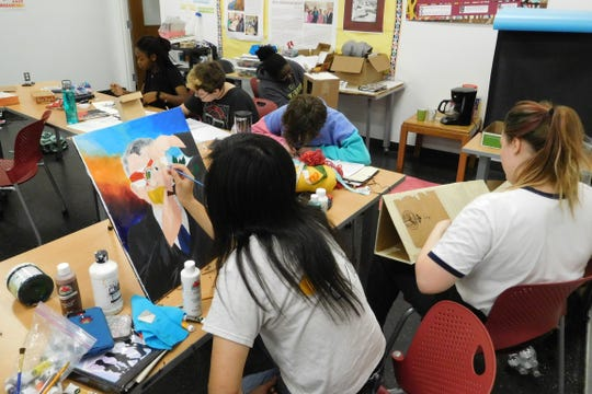 Sissi Zhang paints a tribute to LeRoy Collins while other campers work on their artworks.