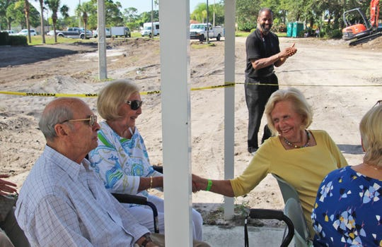 Joan Woodhouse shakes the hand of Nancy Johnson at the Gifford Youth Achievement Center expansion project ground breaking on June 28.  Both ladies spearheaded the building of the Gifford Aquatic Center. Also in photo, Roy Johnson, seated, and Freddie Woolfork, standing.