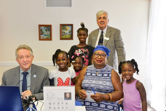 Barbara Wright's grandchildren have their photos and fingerprints taken as part of the New York Life Insurance Co.'s Child ID program with Julio Estrada and James H. Drake at First Baptist Church of Fort Pierce and River of Life Fellowship's joint Back 2 School Bash.