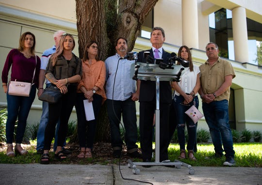 Attorney Evan Fetterman (right of center) announces the wrongful death lawsuit filed against accused killer Austin Harrouff on behalf Michelle Mishcon Stevens' family — gathered around him — on Tuesday, Aug. 7, 2018, outside Martin County's Peter L. Cheney Courthouse and Constitutional Office Center in Stuart.
