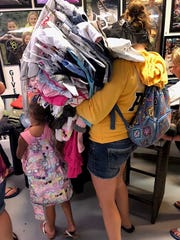 A mother gets free back-to-school clothes for her children at the July 28 Street WearHouse FreePop Up Store at Hope Central.