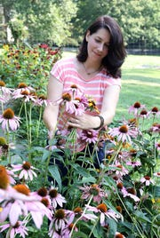 Lynn Trotta of Mount Kisco, who does ceremonial consultation design for women, thinks the concept of a period party is beneficial for both girls and the culture. Trotta cuts flowers from her garden Aug. 7, 2018 in Mount Kisco.