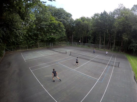 Boys play volleyball tennis at the site of Orangetown's planned recreation center in Orangeburg Aug. 7, 2018.
