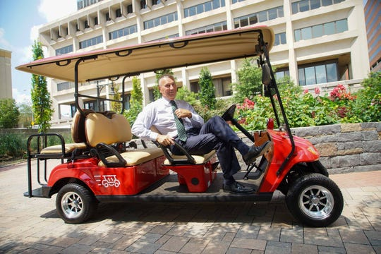 Mayor Mike Purzycki poses for a photo shoot with the new WilminGo golf cart created through a partnership between Buccini/Pollin Group and the University of Delaware's Horn Program that will transport passengers around the N. Market St. area.
