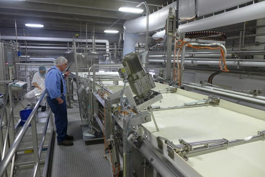 Klondike's largest seller is feta, made in the automated production line. On left, milk pumped into the far vat cells will shuttle along until it is cut into chunks and drained off in the forms shown at right.