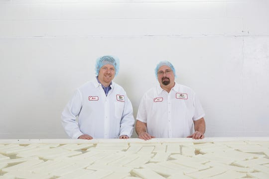 Matt Erdley and Ron Buholzer, the newest master cheesemakers, stand in front of the brine tank holding muenster cheese during processing.