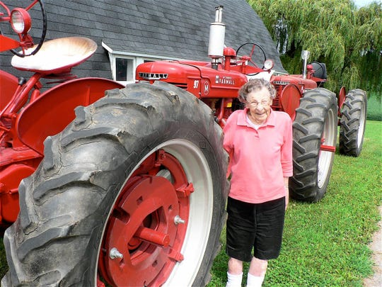 "Lucy Nottestad, Utica, 95 years young, poses with the four Farmall M tractors that her sons use in the yearly tractor pull. Son Ron bought and restored them over the years. ""The yearly tractor pull is a family competition for us,"" he says."