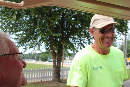 Darrel Cubbison converses with a county fair vendor, as preparations are underway the 2018 Muskingum County Fair.