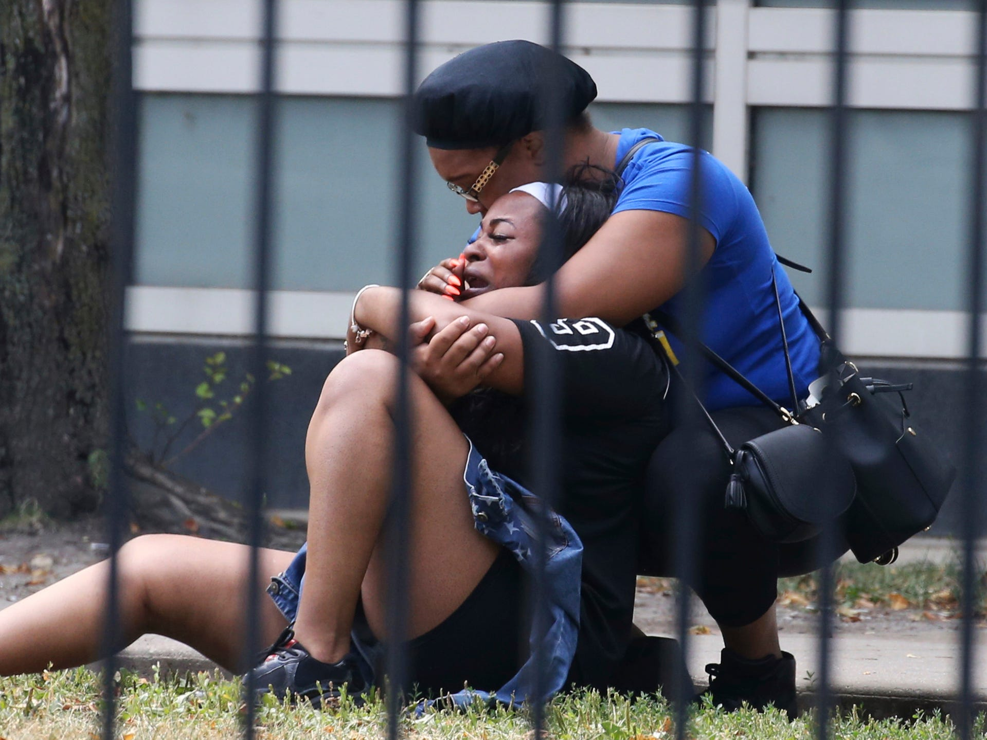In this Sunday, Aug. 5, 2018 photo, two women cry outside the Stroger Hospital in Chicago after they were asked to leave due to overwhelming crowds of family and friends of shooting victims.