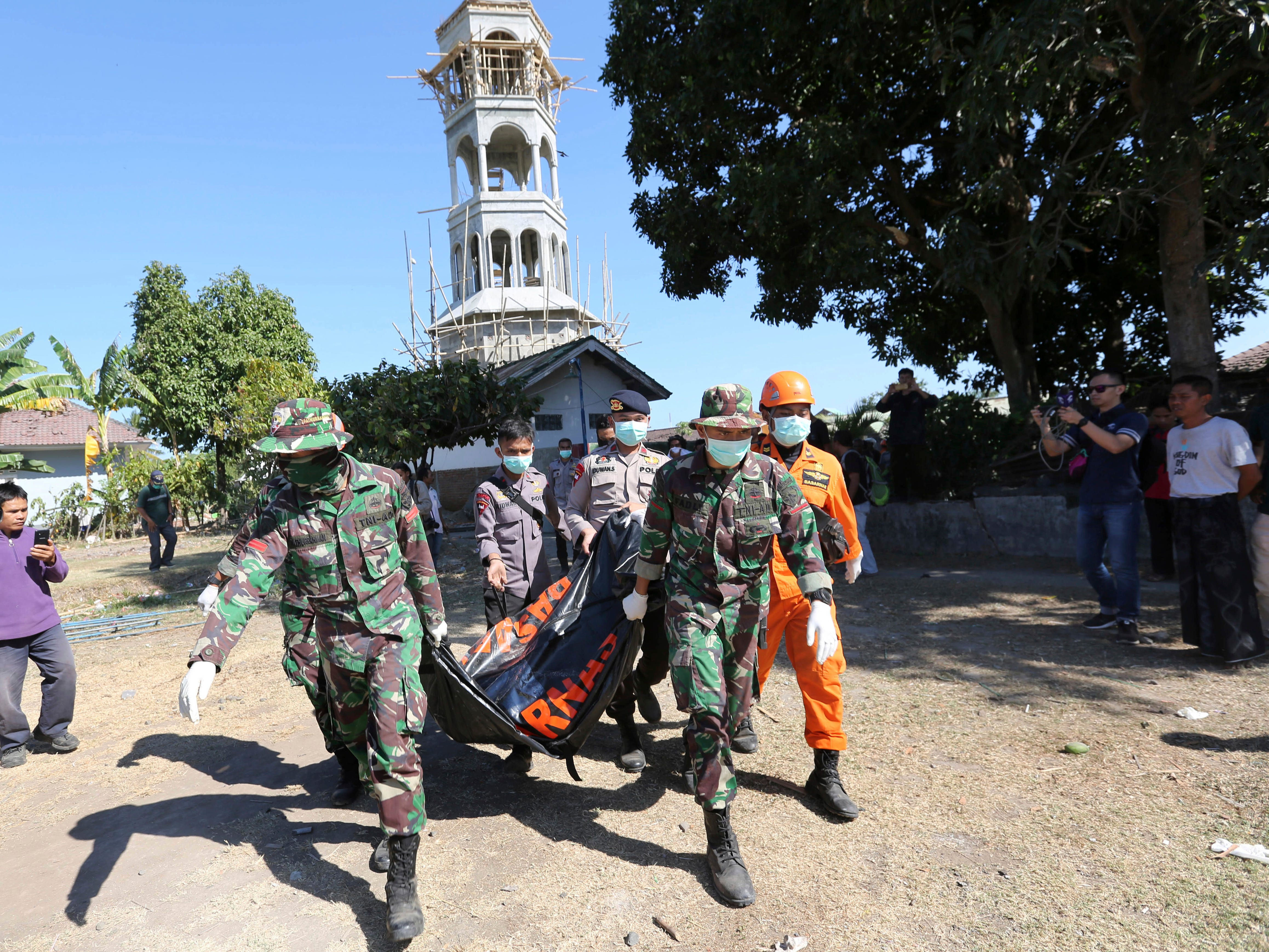 Rescuers carry a body of an earthquake victim recovered from the collapsed Jabal Nur Mosque in North Lombok, Indonesia, Tuesday, Aug. 7, 2018.