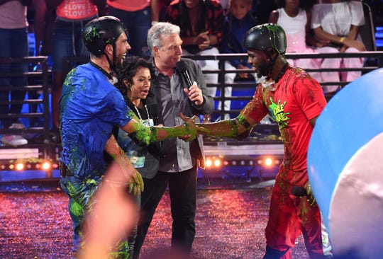 """Swimmer Michael Phelps, from left, Liza Koshy and Marc Summers congratulate host Chris Paul, right, after his """"Double Dare"""" obstacle course challenge win at the Kids' Choice Sports Awards on  July 19."""