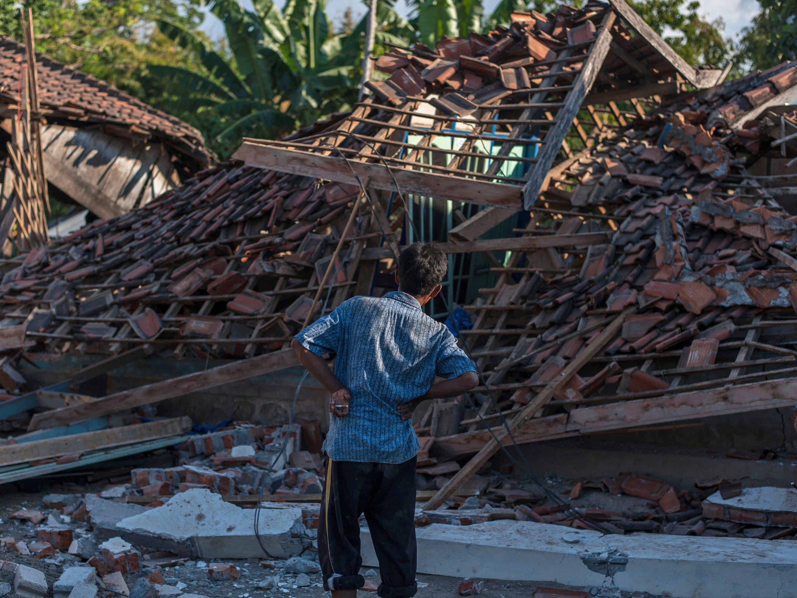 A man inspects the ruins of houses at a village affected by Sunday's earthquake in Kayangan, Lombok Island, Indonesia, Tuesday, Aug. 7, 2018. The north of Lombok has been devastated by the magnitude 7.0 quake that struck Sunday night, damaging thousands of buildings and killing a large number of people.